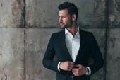 handsome macho man in suit adjusting jacket and looking away
