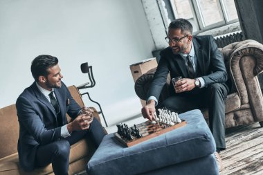 handsome men in full suits playing chess and smiling while sitting indoors
