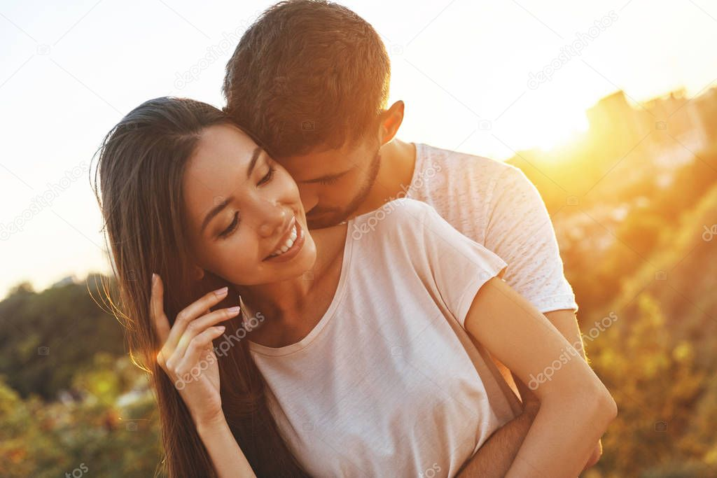 beautiful young couple embracing outdoors, man hugging woman