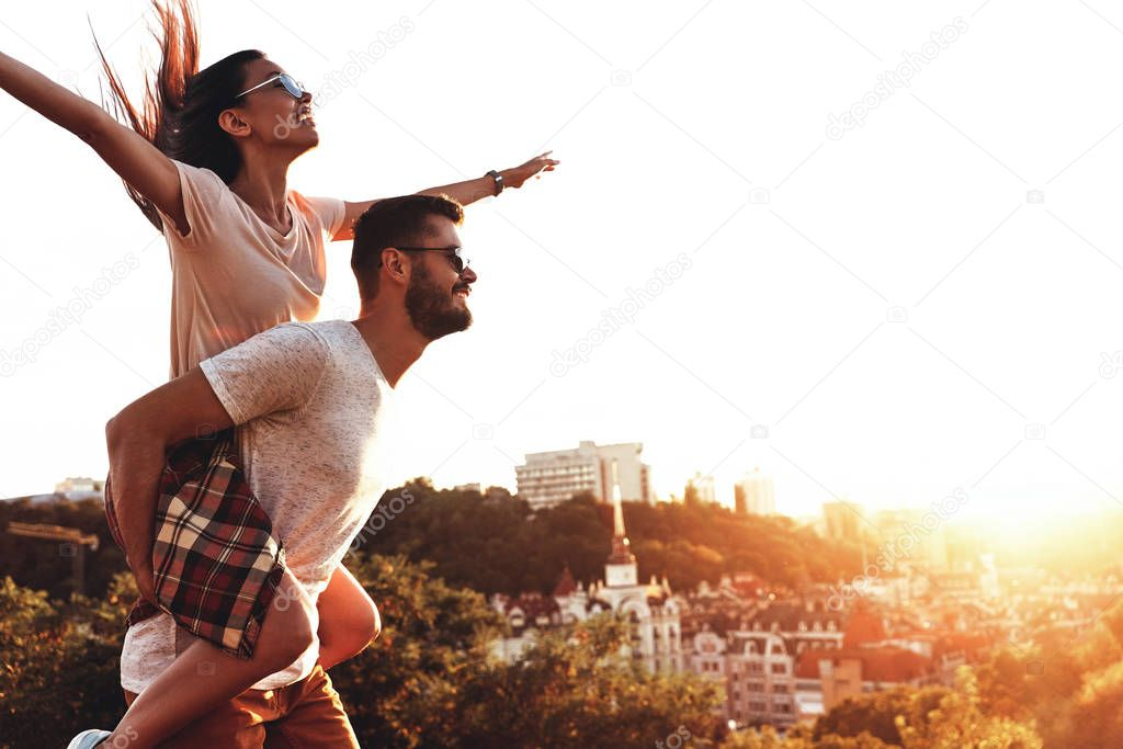man giving his girlfriend piggy back ride outdoors