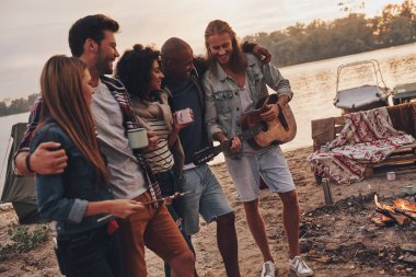 best friends enjoying beach party near campfire with drinks and guitar
