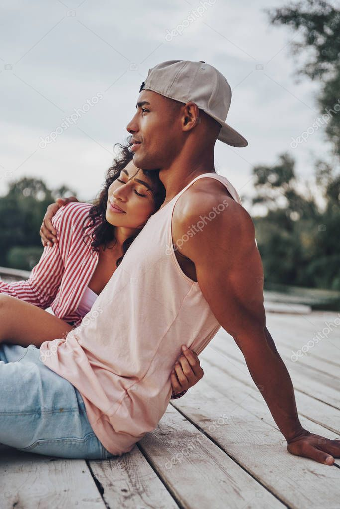 romantic couple in love embracing and sitting on pier at lake