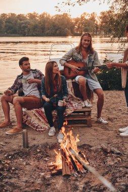 gençlerin rahat kıyafet adam gitar çalmak batımında, göl kenarında kamp zevk