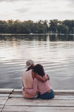 back view of romantic couple sitting on pier at lake