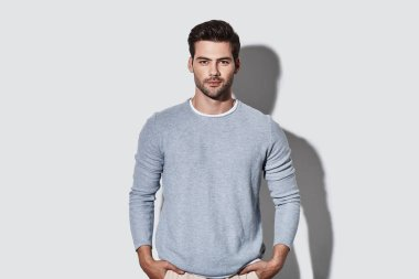 handsome young man in casual wear looking at camera and smiling while standing against grey background