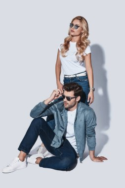 fashionable man and woman in denim wear posing in studio, copy space