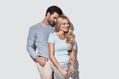 Loving caucasian couple embracing and smiling in studio