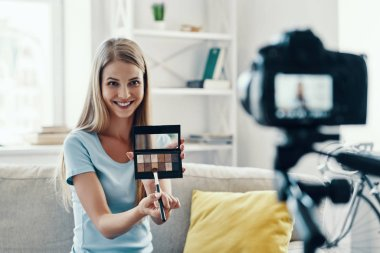 Beautiful young woman smiling and applying make-up pallet while making social media video at home stock vector