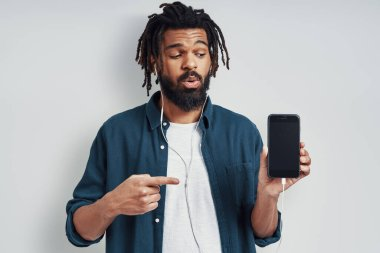 Charming young African man in casual wear pointing copy space and listening music while standing against grey background