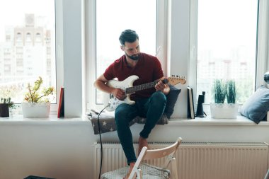 Handsome young man in casual clothing playing guitar while sitting on the window sill