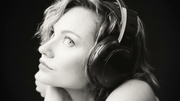 Black and white portrait of a young girl in headphones. Young beautiful girl enjoying music. Relaxation, emotions, rest.