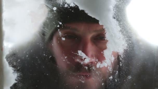 Ein Mann wischt den Schnee und zieht im Winter auf das gefrorene Glas. Porträt eines Mannes, der vom Hof aus durch ein Fenster blickt.
