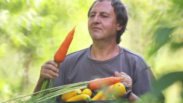 Male farmer with a basket of fresh vegetables. A man eats fresh vegetables, tomato, carrots, cucumber.