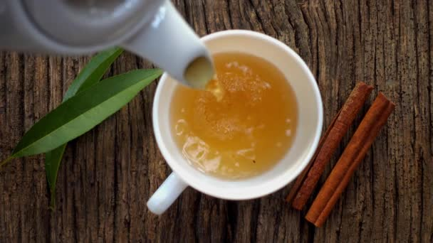 Natural, hot, fresh tea with spices is poured into a mug, top view.