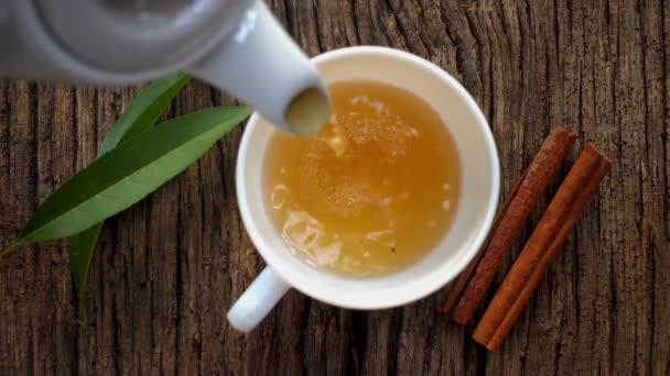 Přírodní, horký, čerstvý čaj s kořením se nalije do džbánu, pohled shora.