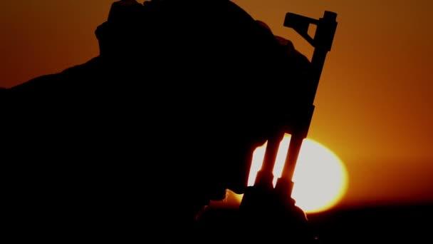 Porträt eines muslimischen Kriegers, der seinen Kopf über ein Maschinengewehr beugt. Militante Islamisten beten mit Maschinengewehr zu Allah.