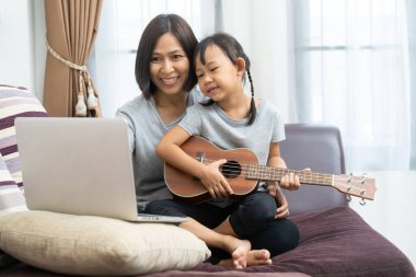 Asian mother and daughter using laptop studying to play ukulele at home