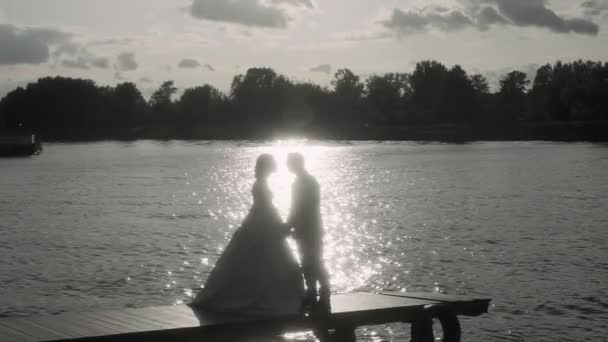 strength of the bride and groom who stand by the water in the sunset in the backlight