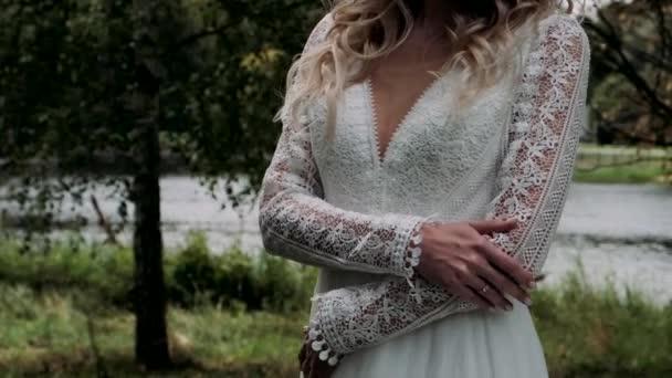 Egy fehér ruhás lány megdermedt és felmelegíti a kezét.