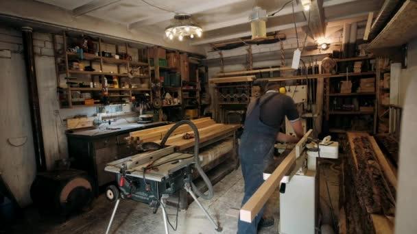 Tischler in der Werkstatt. Der Mensch arbeitet mit Holzwerkstoffen. Tischler, der in einer Werkstatt mit Holzhandwerk beschäftigt ist, um Baumaterial oder Holzmöbel herzustellen. Der junge Schreiner setzt professionelles Werkzeug ein