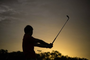 silhouette asian golfer playing golf during beautiful sunset,Thailand people