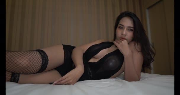 ázsiai érzékeny lány harisnya és áttetsző ruha pózol az ágyon