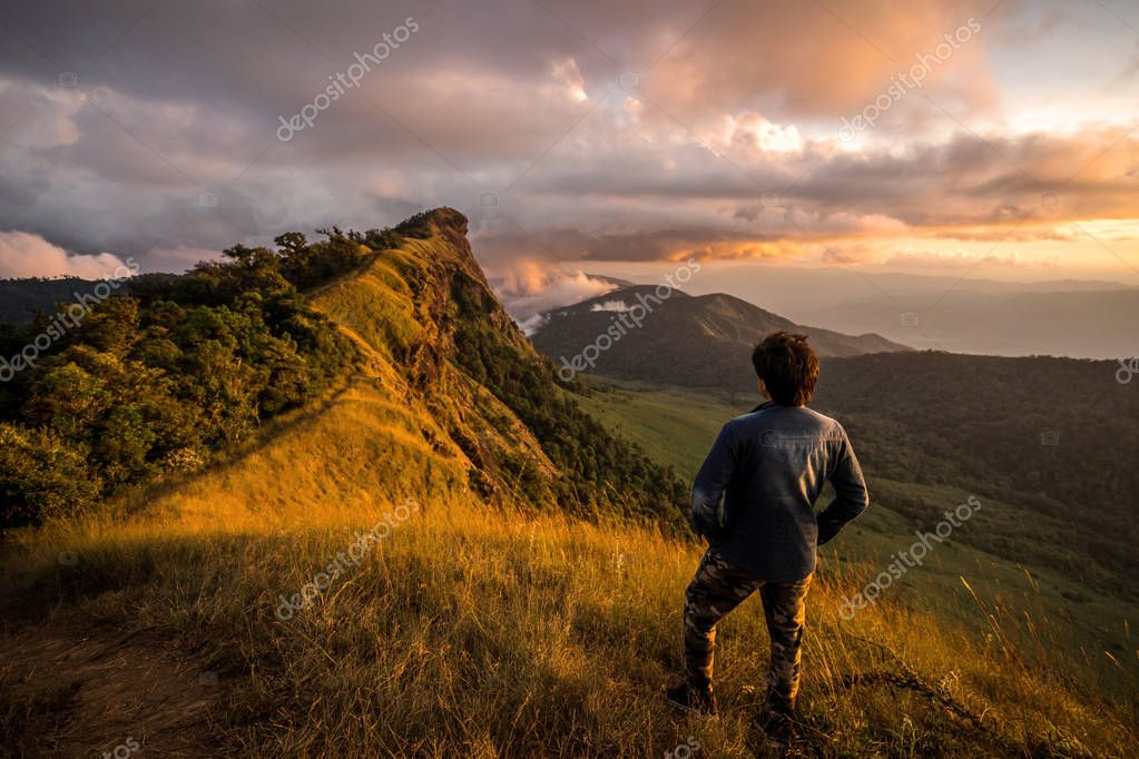 Young traveler looking at beautiful sunrise over the mountain at monjong, Thailand