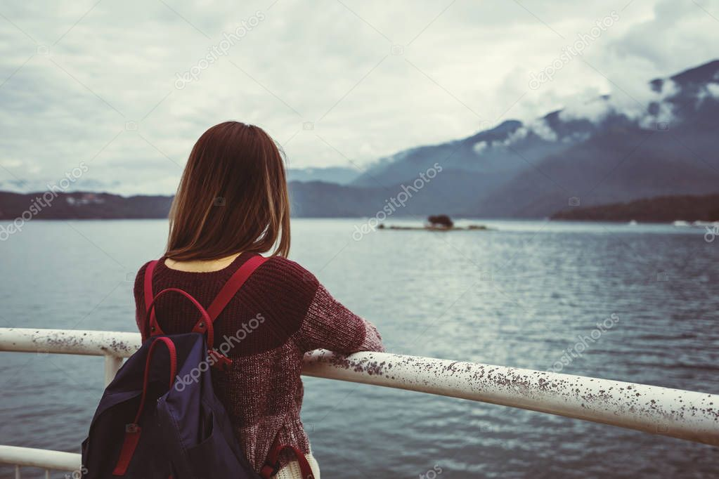 Lonely woman traveler standing absent minded and looking at the river