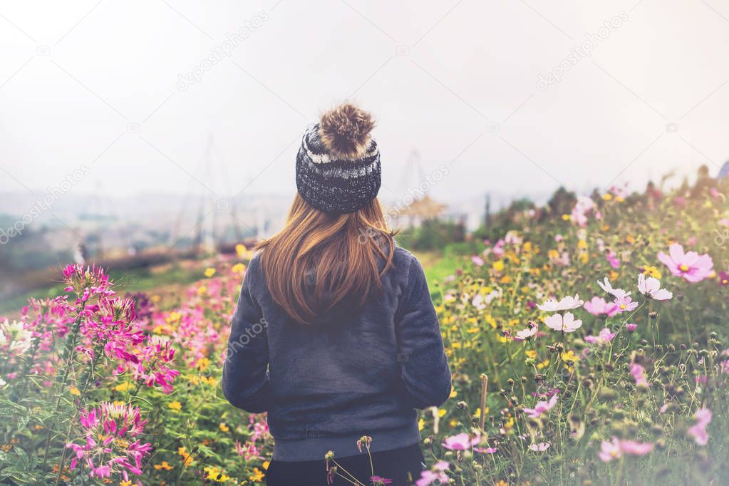 Young woman traveler walking in the flower field on the mountain