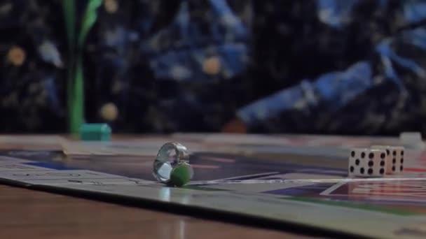 Detailní záběr rukou lidí, kteří hrají hru Monopoly.
