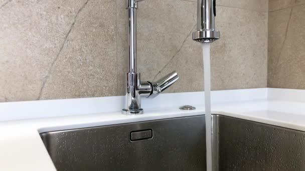 Nő kézzel kapcsolja króm csaptelep és a víz folyik a mosogató, után a nő kezét cserél rendszer