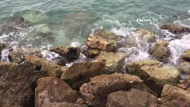Erős hullámok fröccsen, kövek alatt. Tengeri hullámok ütő sziklás partján. Óceán fröccsenés ellen, sziklákon