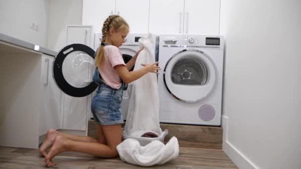A tinédzser lánya házimunkát végez a mosodában, és szennyest tesz a mosógépbe. A lány segít az anyjának. Lassú mozgás.