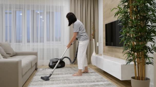 Junge Frau staubsaugt im Wohnzimmer