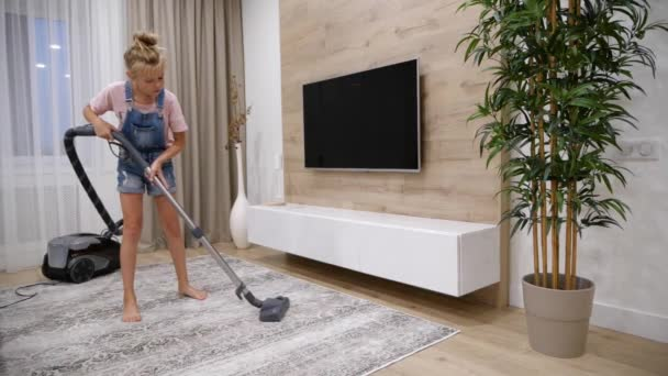 Preteen girl help to clean living room with staubsauger help mother with pures