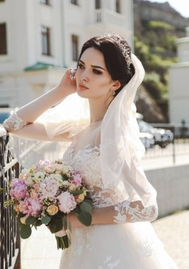 fashion photo of beautiful bride with dark hair in elegant wedding dress posing outdoor with tender bouquet of flowers