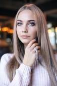 gyönyörű fiatal nő, elegáns ruhákat kávézóban ülve hosszú szőke haj divat fotó