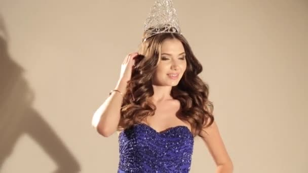 video of beautiful woman with dark hair in luxurious dress and precious crown posing in studio