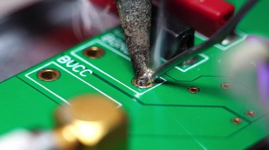Engineer or technician repairing electronic circuit board with soldering iron