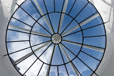 Round roof window with a view of the sky and clouds