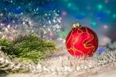 Červené vánoční koule a větve jedle na pozadí světla věnec
