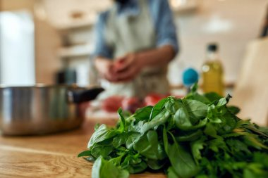 Close up of basil lying on the table. Young man cook preparing healthy meal with vegetables in the background. Italian cuisine concept