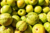 Čerstvé organické zelené a zralé guavy a jablka pozadí