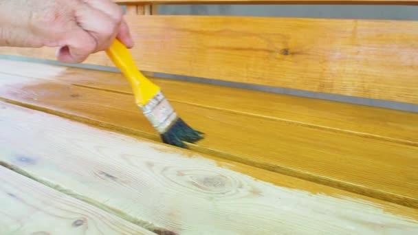 Malování dřevěné lavičky s ochranným proti povětrnostním vlivům. Ženská ruka aplikuje žlutou impregnaci štětcem. Povrchová úprava od hmyzu. Koncept DIY. Zavřít.