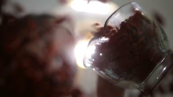 Mladá žena rozptyl goji bobule ve skleněné míse