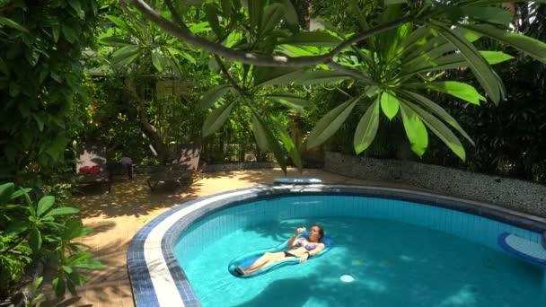 Mladá žena ležící na vodní matraci v bazénu na slunečný den