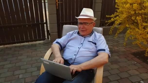Senior tippt auf Laptop an Strauch mit gelben Blüten
