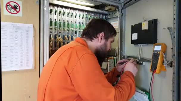 elektrikář kontroluje elektrické napětí v ropném tankovém boxu