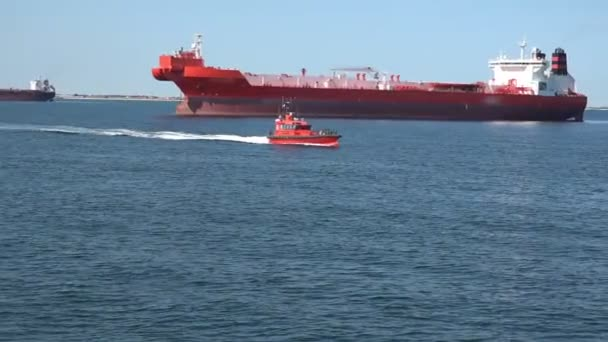 malý pilot motorová loď pluje rychle proti velké červené cisterny