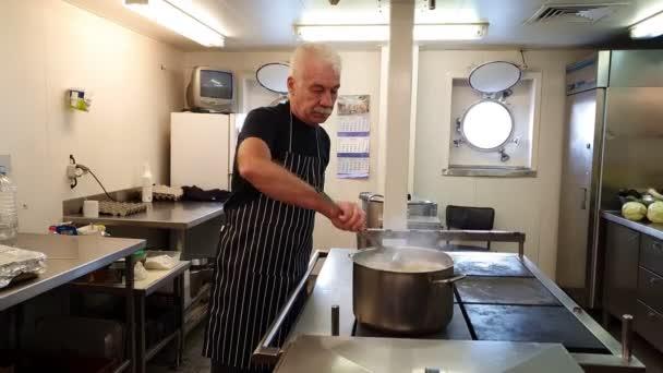 professionelle Köchin in schwarz gestreifter Schürze mixt kochendes Gericht